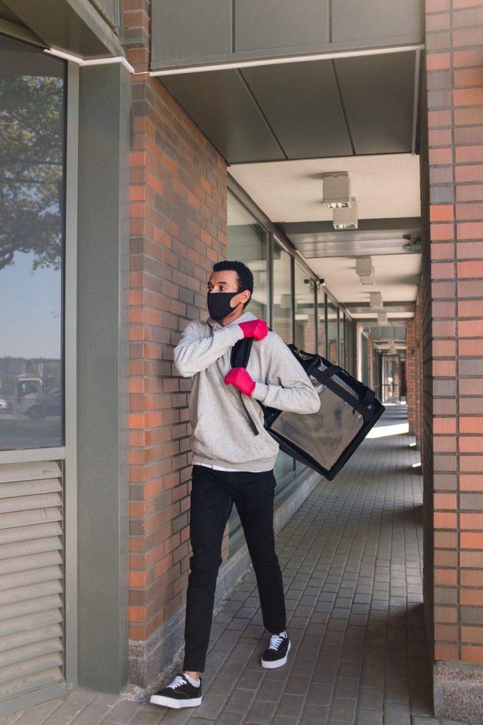 Repartidor con mascarilla y guantes cargando una mochila