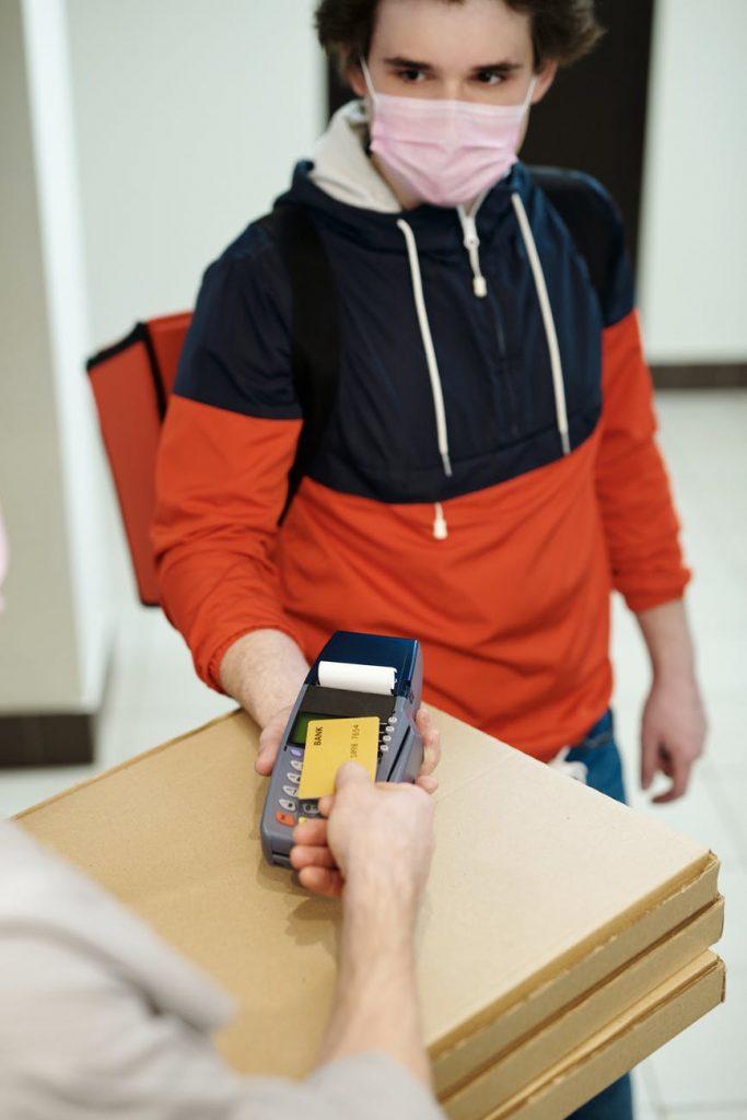 Repartidor entregando pedidos a un cliente que está pagando con el TPV