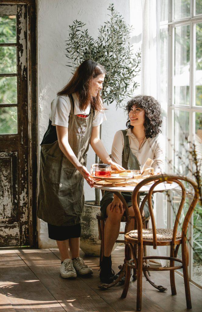 Camarera sirviendo a una chica en la mesa una bandeja con comida y bebidas
