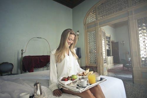 Chica sentada en la cama de la habitación del hotel con bandeja llena de comida