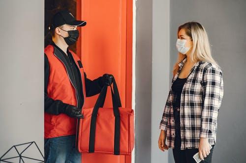 Repartidor entregando una bolsa roja con pedido a una chica