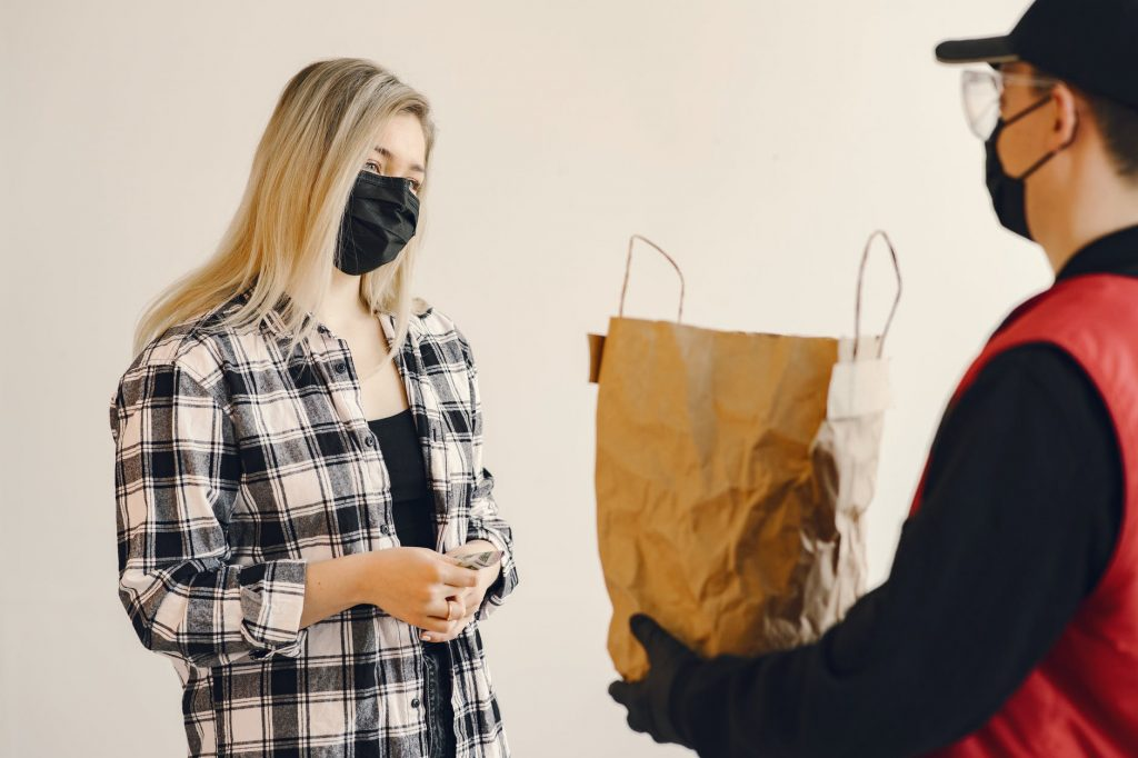 Repartidor entregando bolsa de pedido a una chica que tiene dinero en la mano