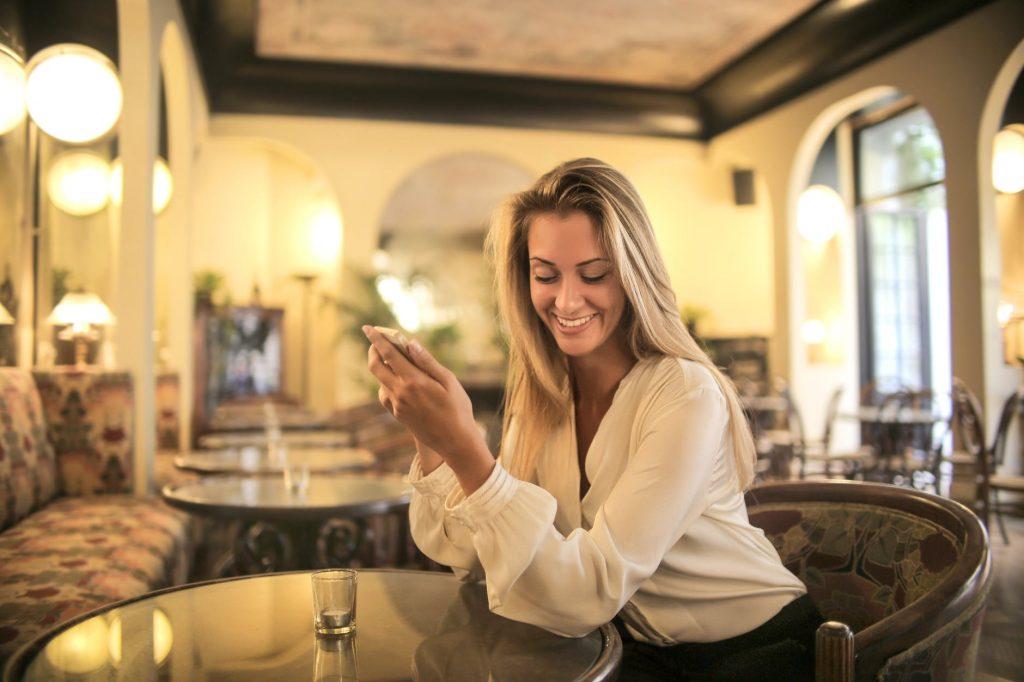 Chica sentada en la mesa del restaurante del hotel mirando el móvil
