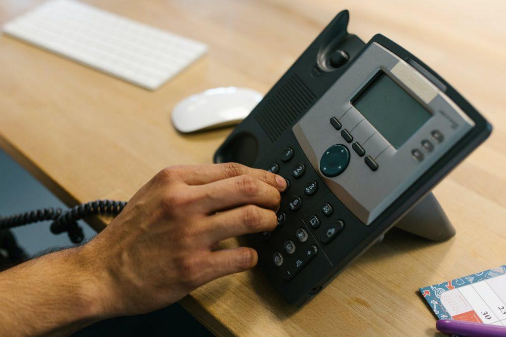 Mano pulsando las teclas de un teléfono
