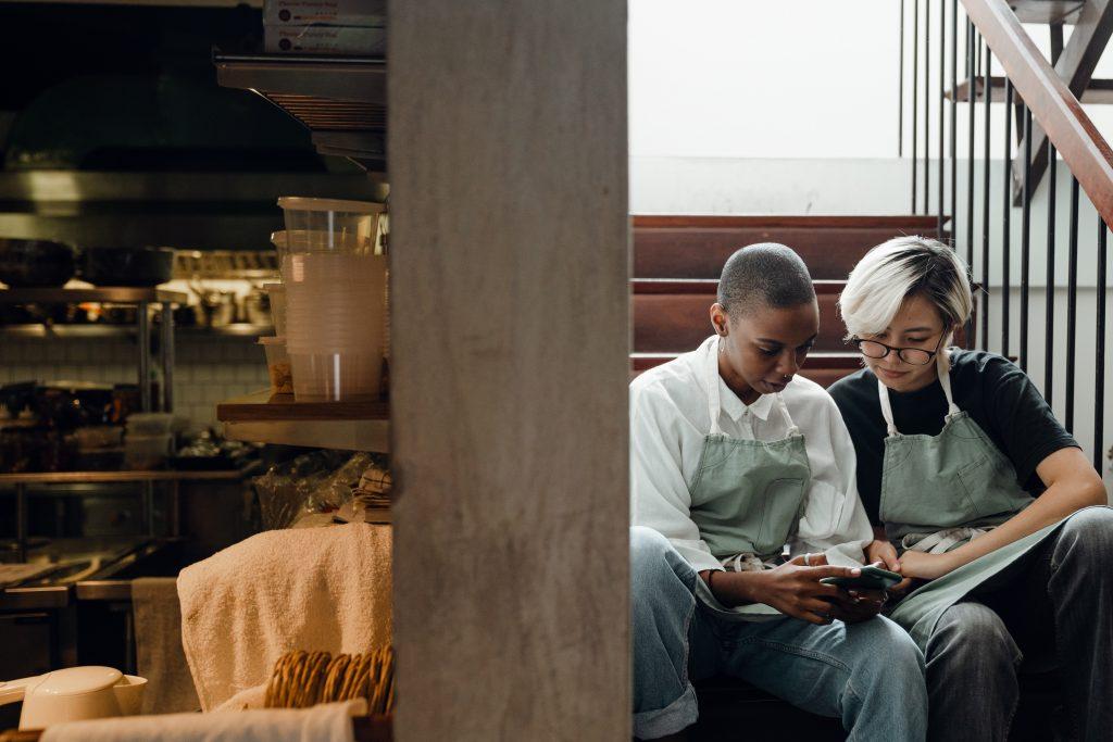 Imagen de dos camareras en un restaurante mirando algo en un dispositivo móvil.