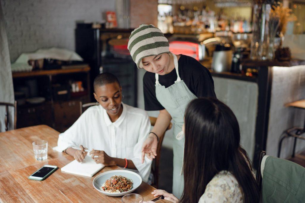 Una camarera atendiendo a dos clientas en el restaurante.