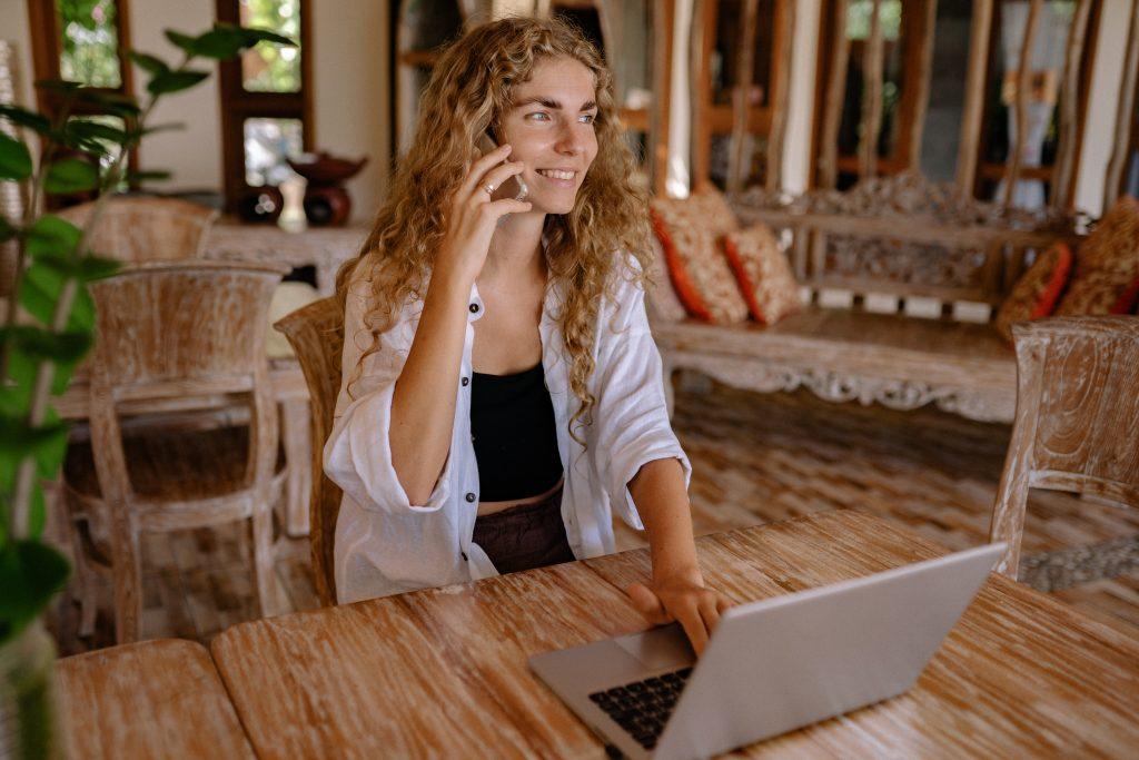 Mujer sentada en una mesa mientras habla por teléfono y consulta su ordenador portátil.